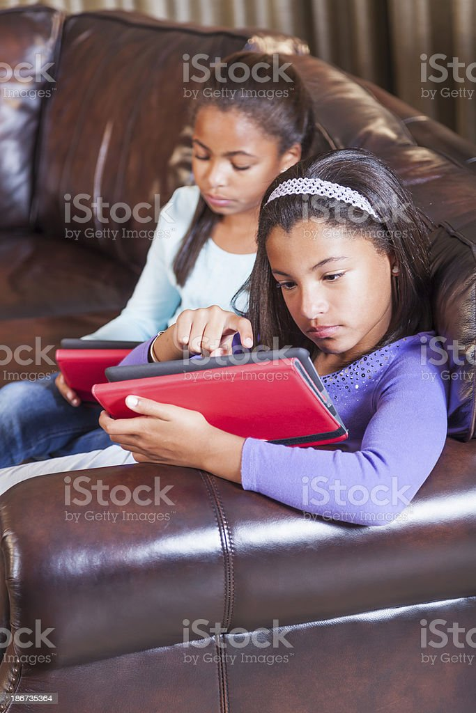 Two children at home using digital tablets stock photo
