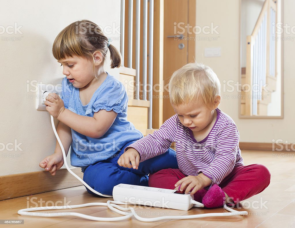 Two children at on floor playing with adapter plug stock photo