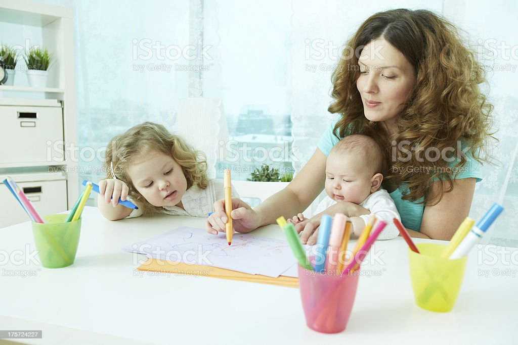 Two children being homeschooled by woman stock photo