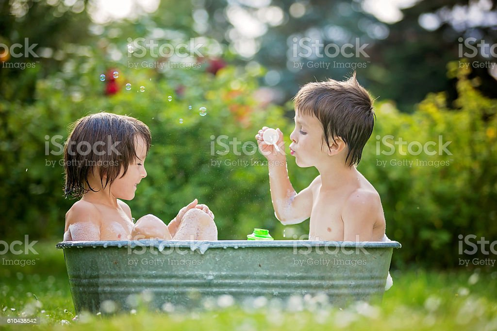 Two children, boy brothers, having a bath outdoors, making soap stock photo