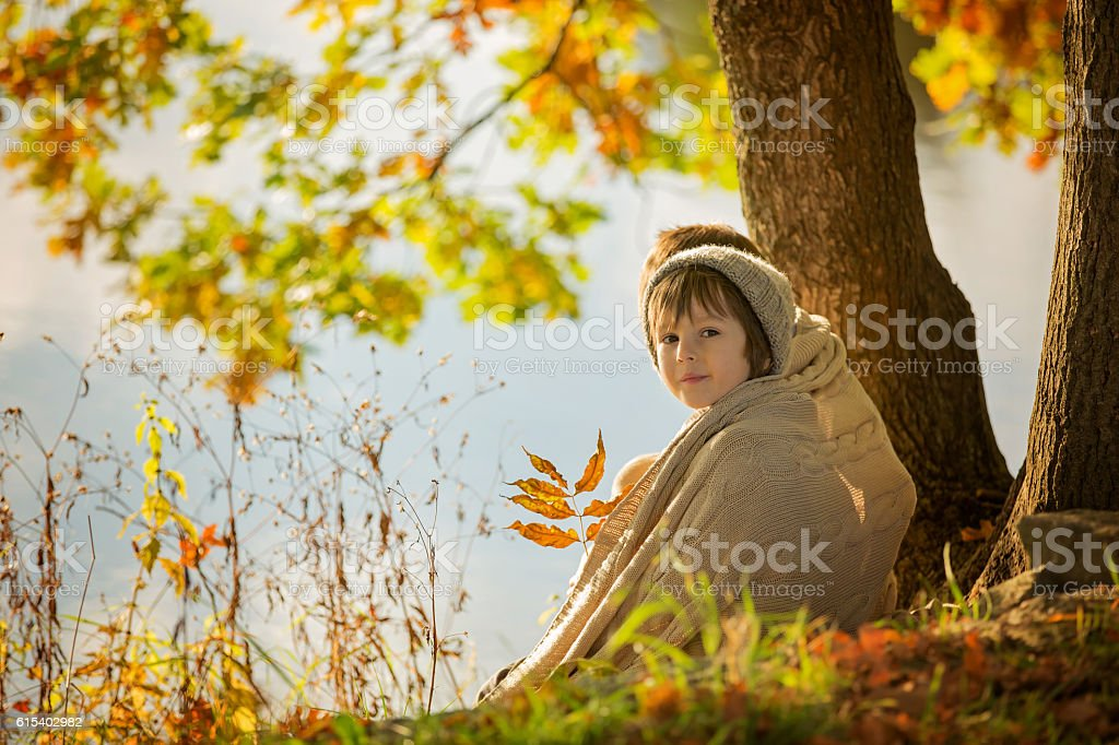 Two children, boys, sitting on the edge of a lake stock photo