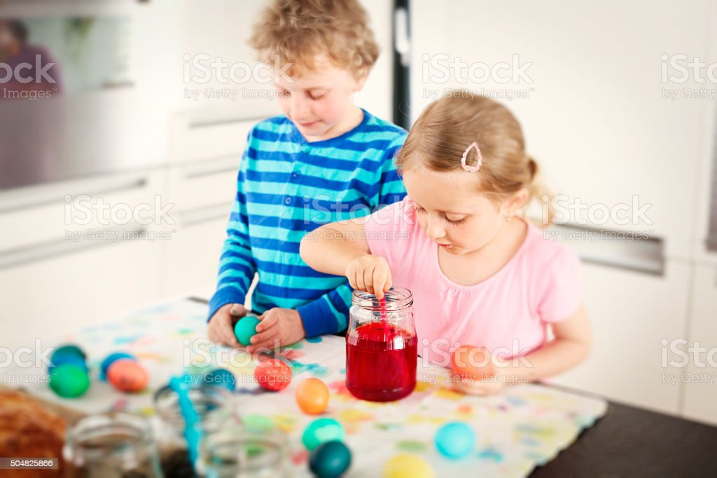 Two children coloring together easter eggs stock photo