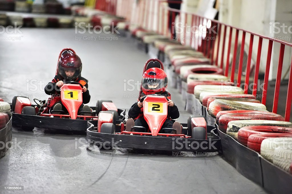 Two children competing on karts at an indoor racetrack stock photo