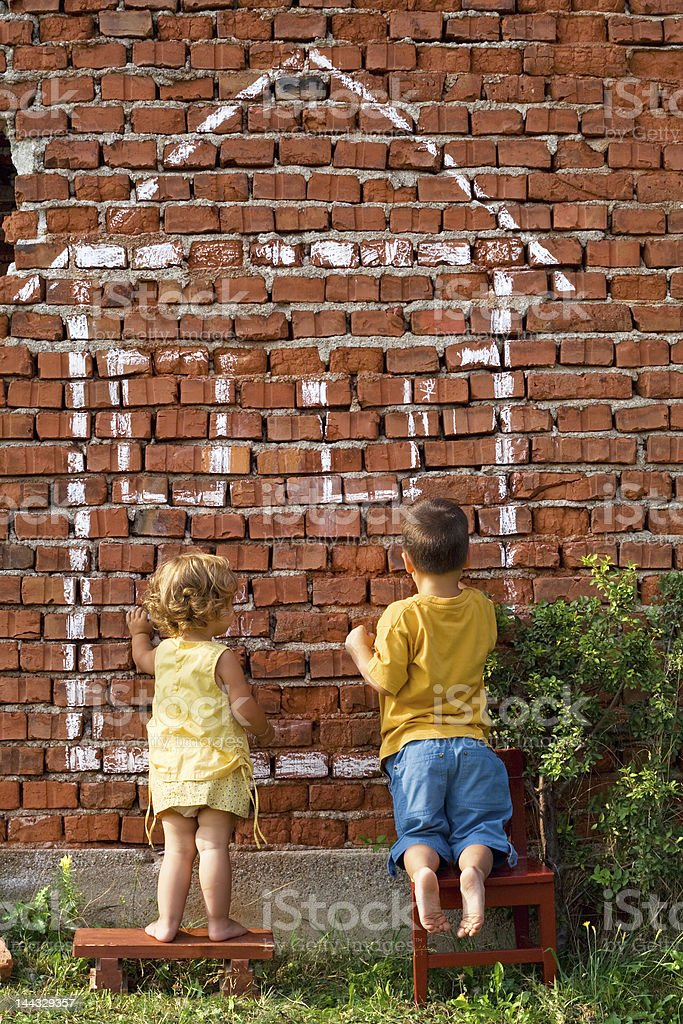 Two children drawing a house royalty-free stock photo