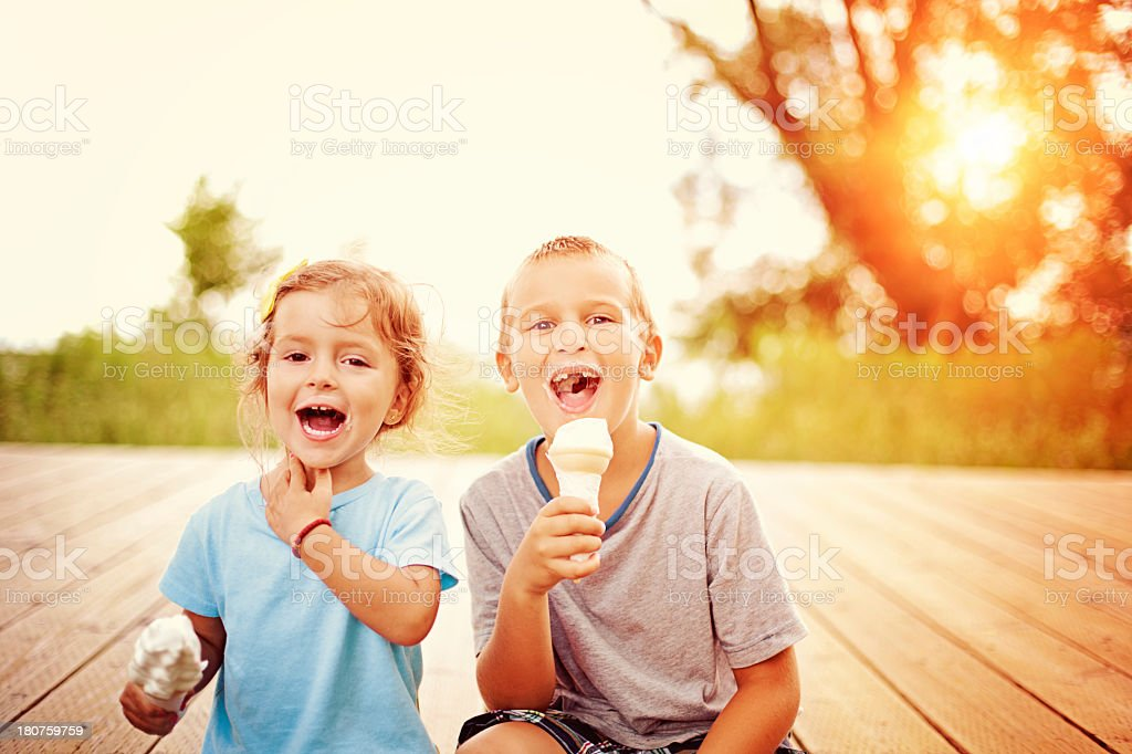 Two children eating ice cream cones stock photo