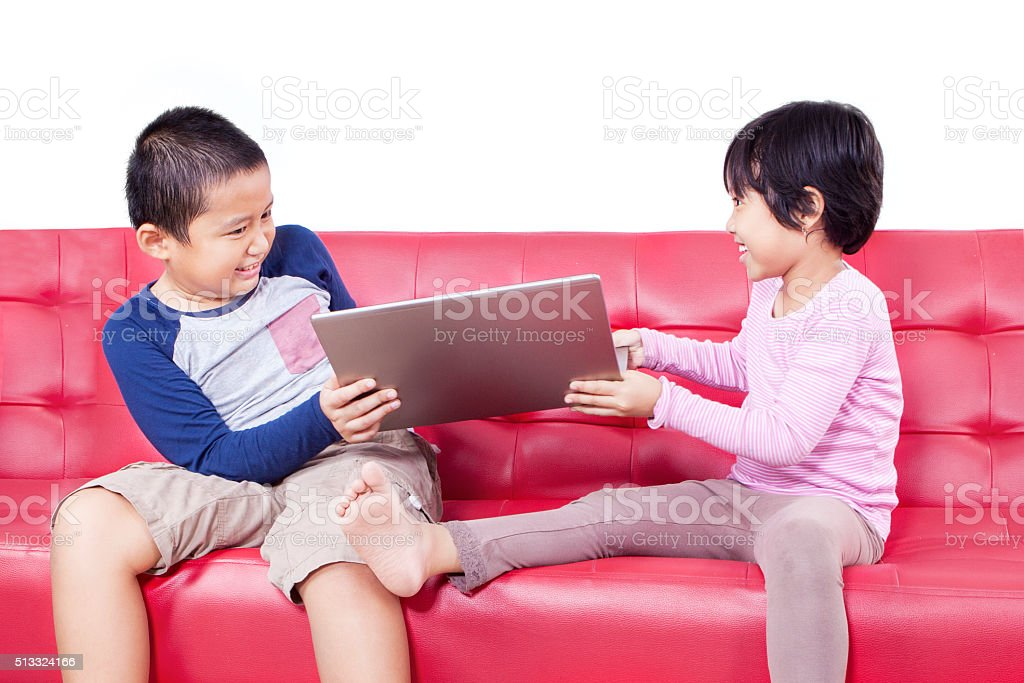 Two children fighting over a laptop stock photo