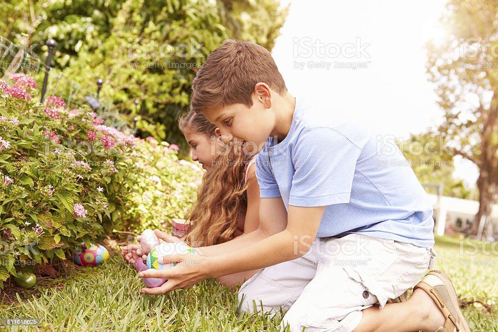 Two Children Having Easter Egg Hunt In Garden stock photo