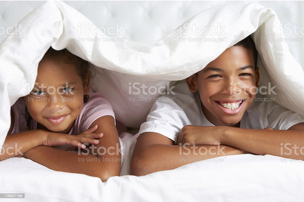 Two Children Hiding Under Duvet In Bed royalty-free stock photo