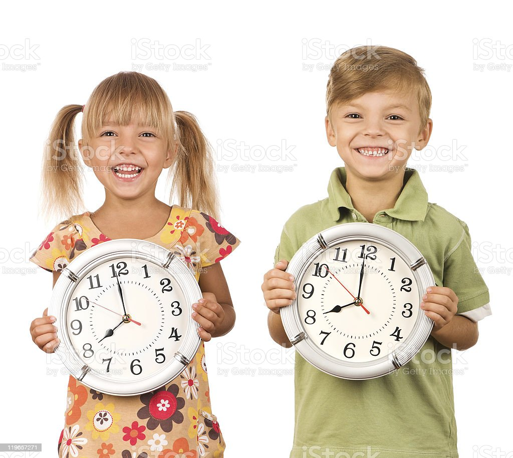 Two children holding clocks and smiling stock photo