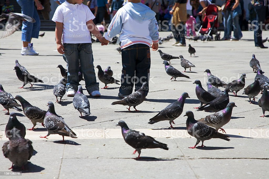 Two children holding hand with pigeons around royalty-free stock photo