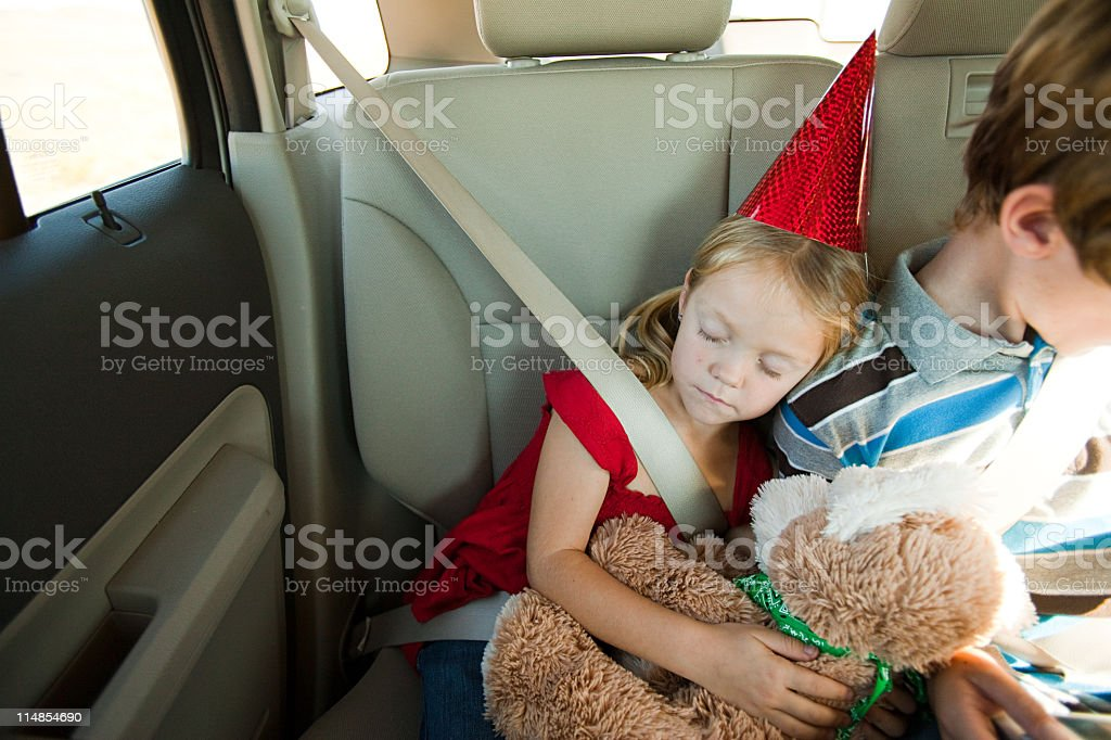 Two children in back seat of car, girl asleep stock photo
