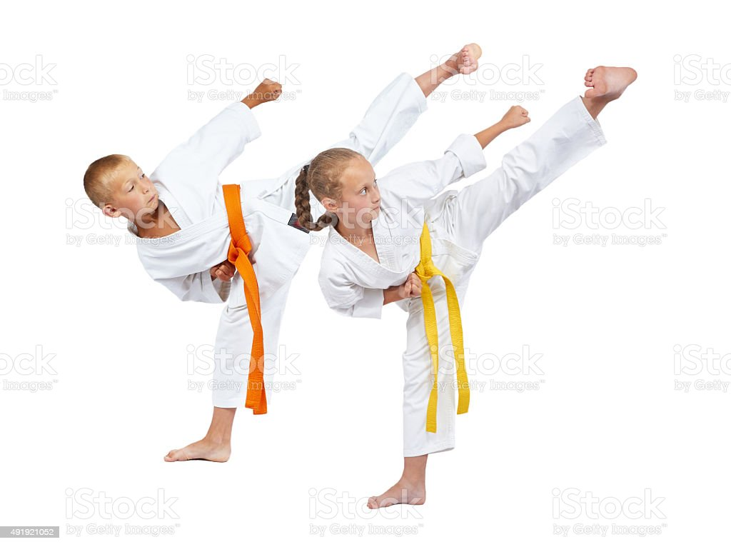 Two children in karategi beats Yoko geri stock photo