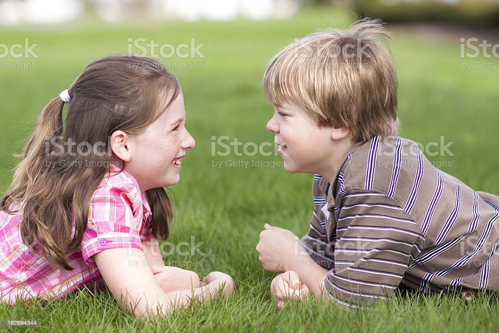 Two children laughing together on grass (Series) stock photo