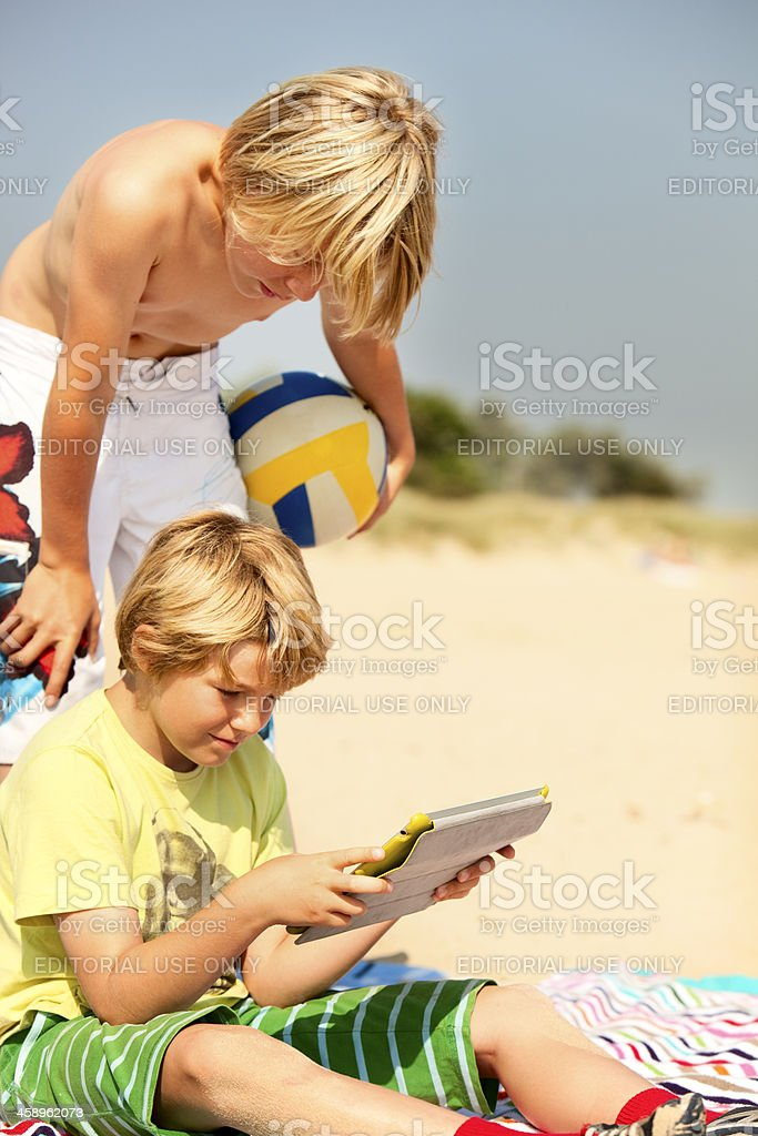 Two children looking at an iPad on the beach stock photo