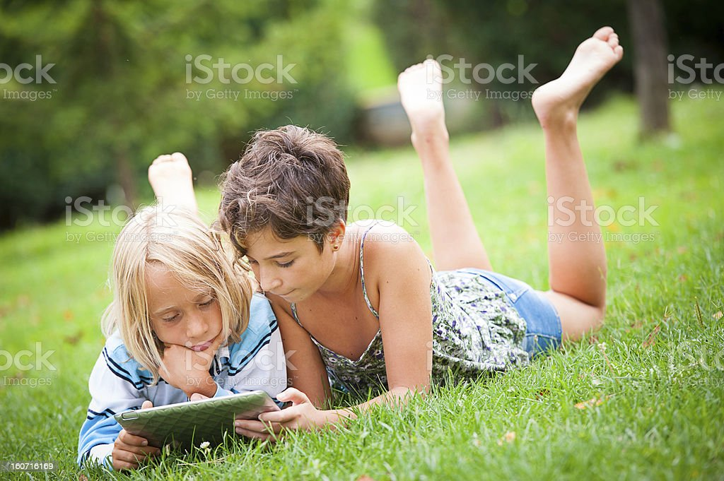 two children lying on the grass lwhit tablet royalty-free stock photo