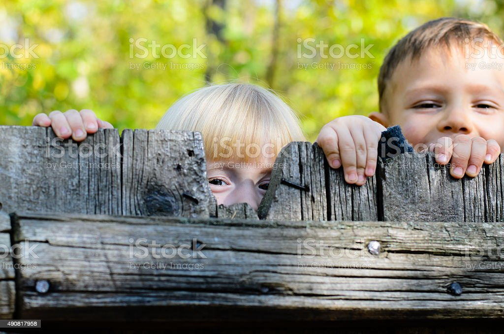 Two children peeking over a wooden fence stock photo