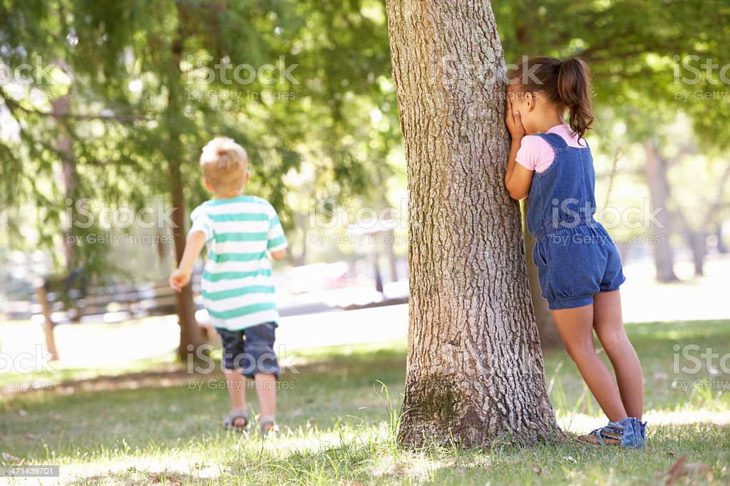 Two Children Playing Hide And Seek In Park stock photo