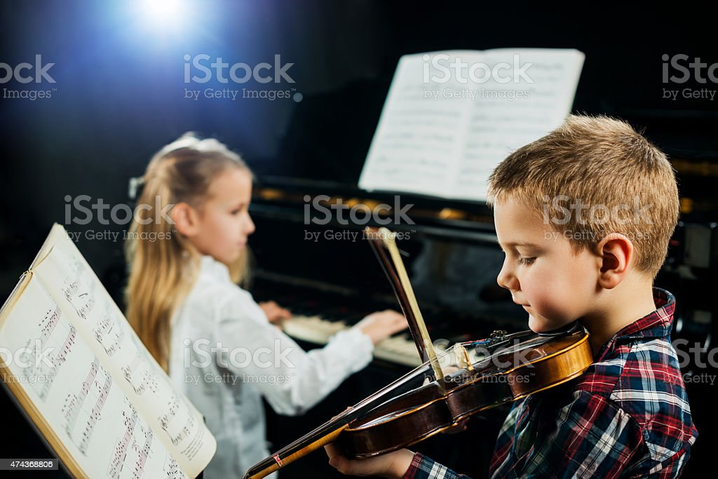 Two children playing musical instruments. stock photo