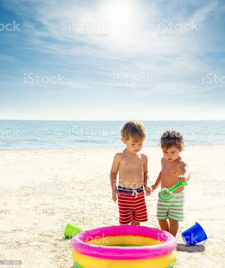 Two children playing on the beach stock photo