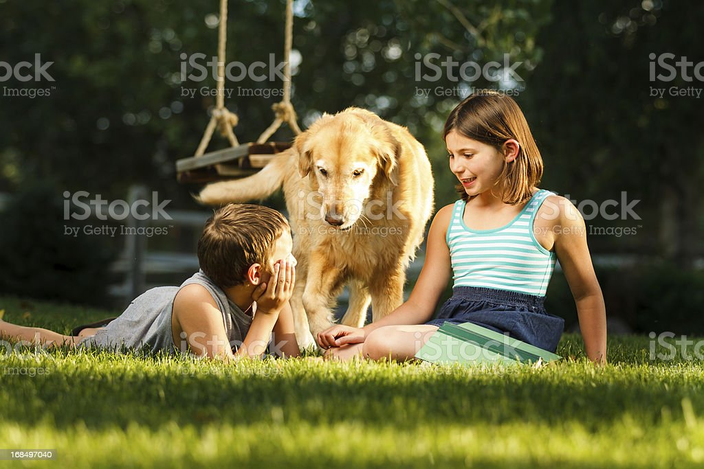Two children playing with dog in the garden royalty-free stock photo