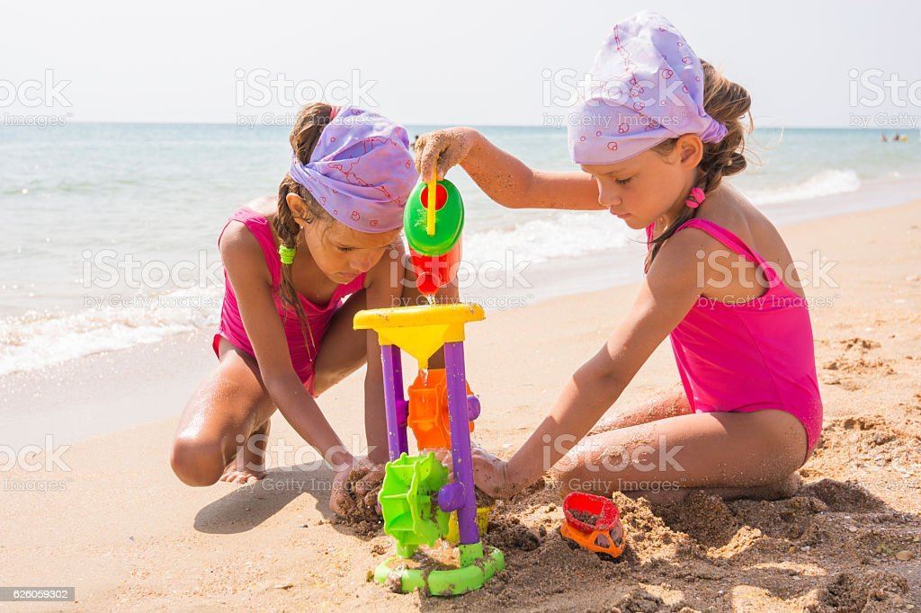 Two children playing with toys in the sand stock photo