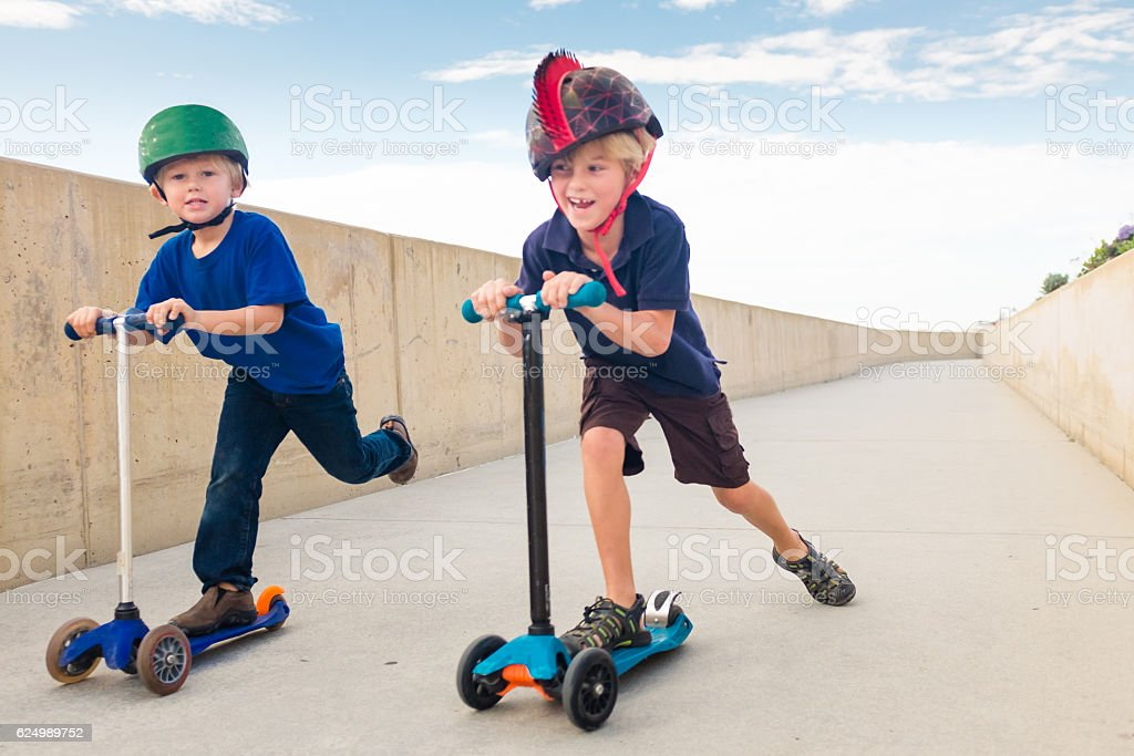 Two Children Racing on Scooters stock photo