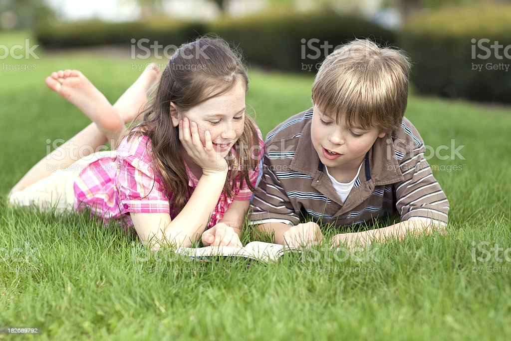 Two children reading book on grass (Series) royalty-free stock photo