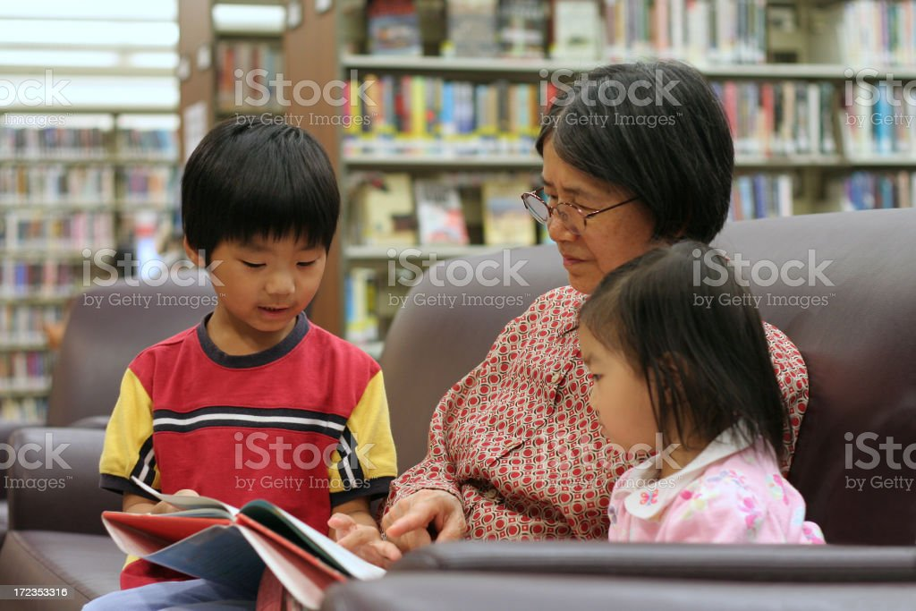 Two children reading with their grandmother in a library royalty-free stock photo