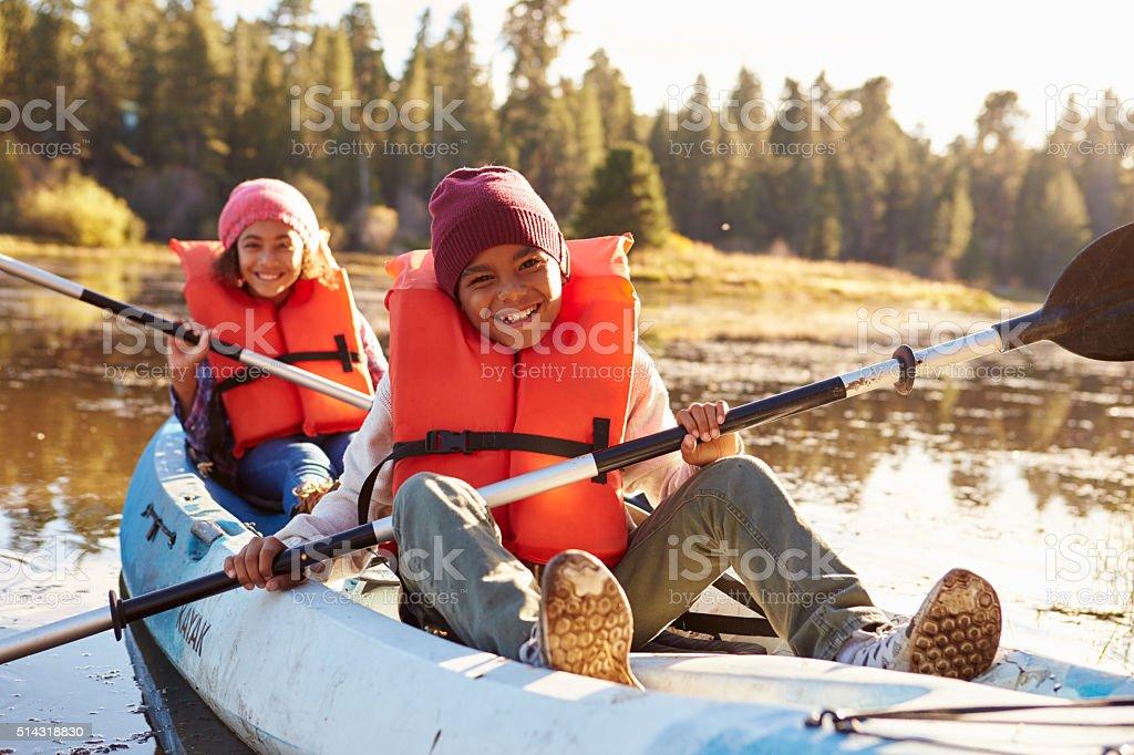 Two Children Rowing Kayak On Lake stock photo