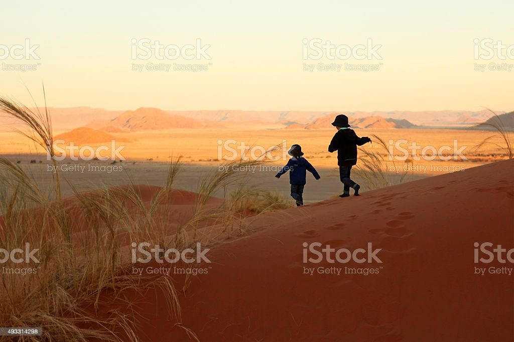Two Children Running Down The Sand Dunes in Sossusvlei Namibia stock photo