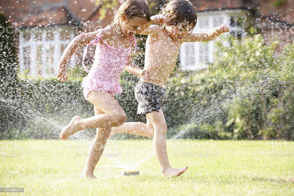 Two Children Running Through Garden Sprinkler stock photo