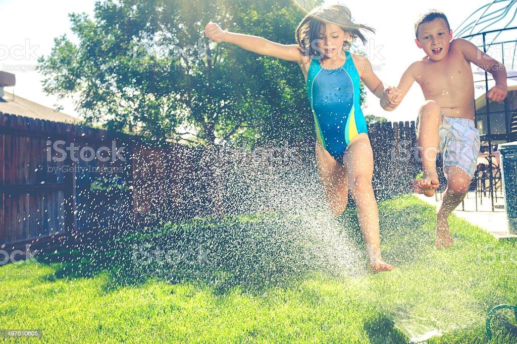 Two children running through lawn sprinklers stock photo