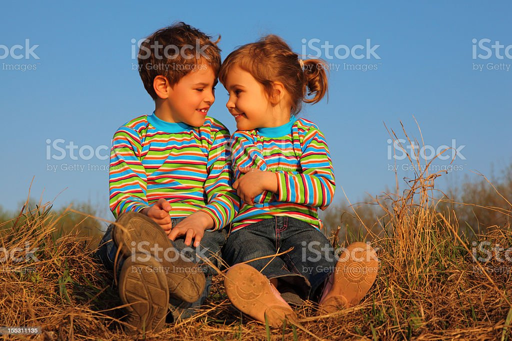 Two children sit on dry grass stock photo