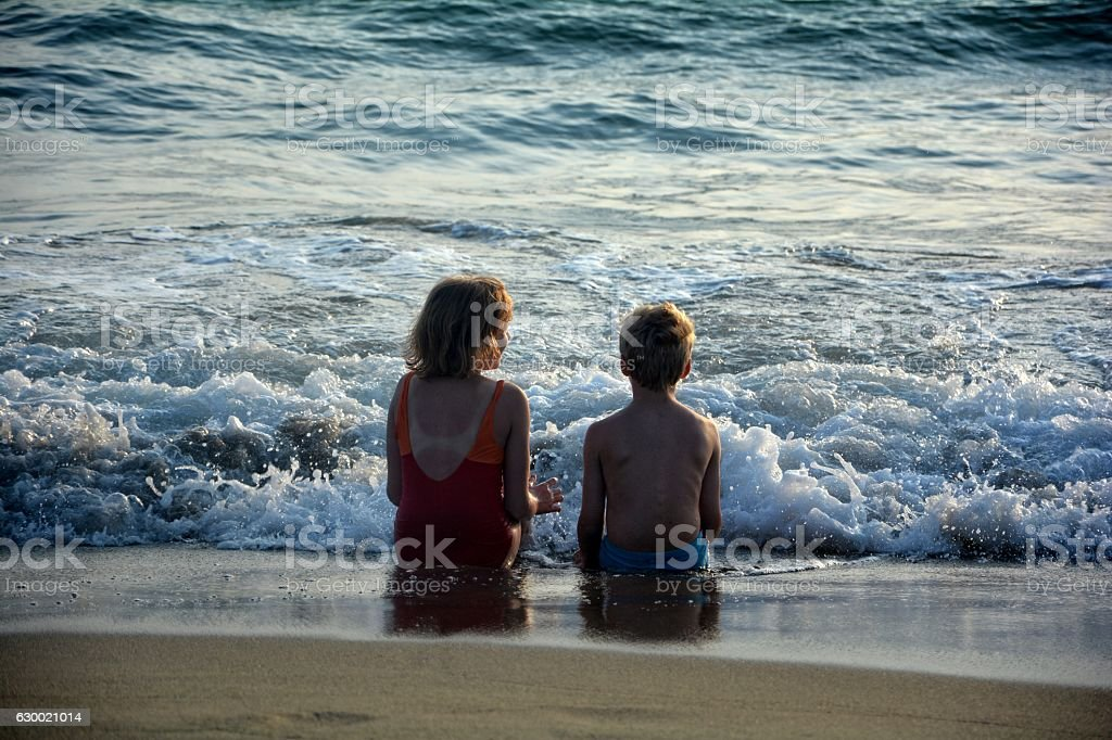 Two children sit on the beach  before the wave stock photo