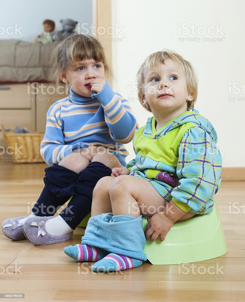 Two children  sitting on chamber pots stock photo
