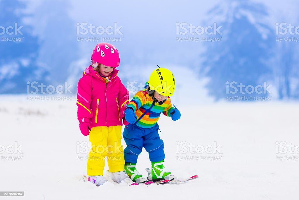Two children skiing in snowy mountains stock photo