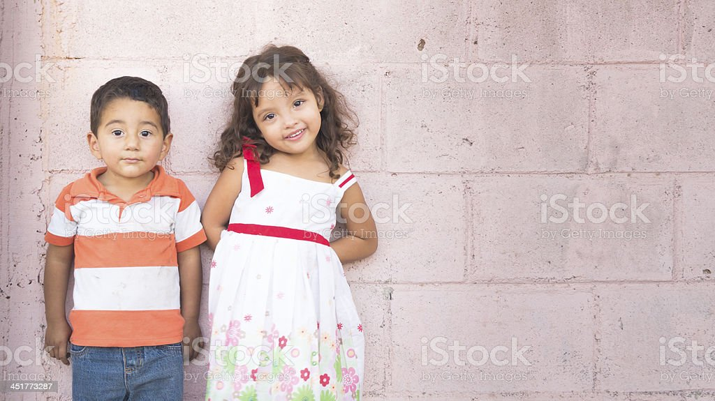 Two children standing next to a wall stock photo