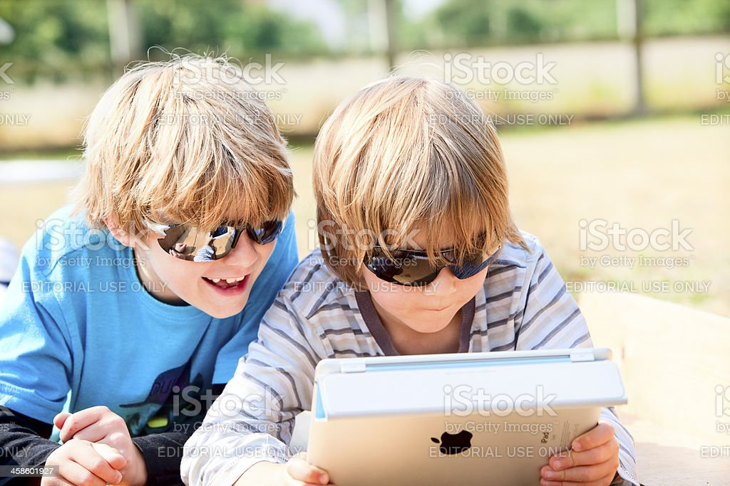 Two children using an iPad outdoors royalty-free stock photo