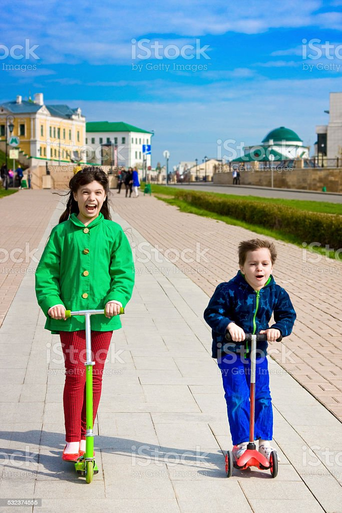 Two children with scooters in spring stock photo