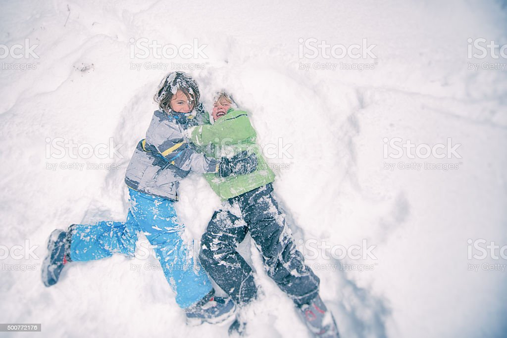 Two children wrestle playfully in the powdery snow stock photo
