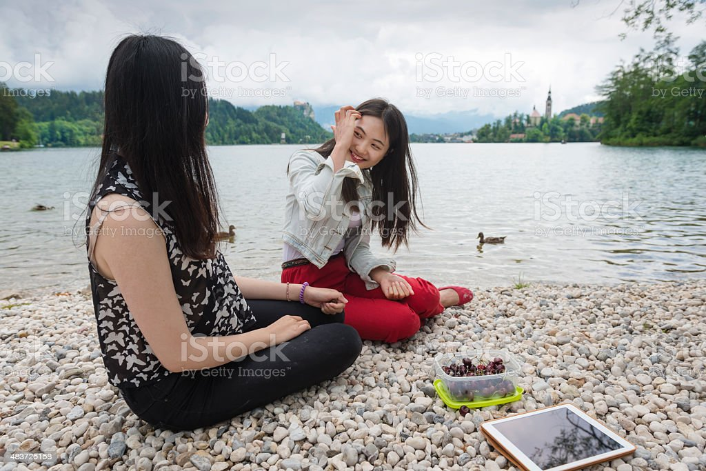 Two Chinese Friends Eating Cherries by Bled Lake, Slovenia, Europe stock photo