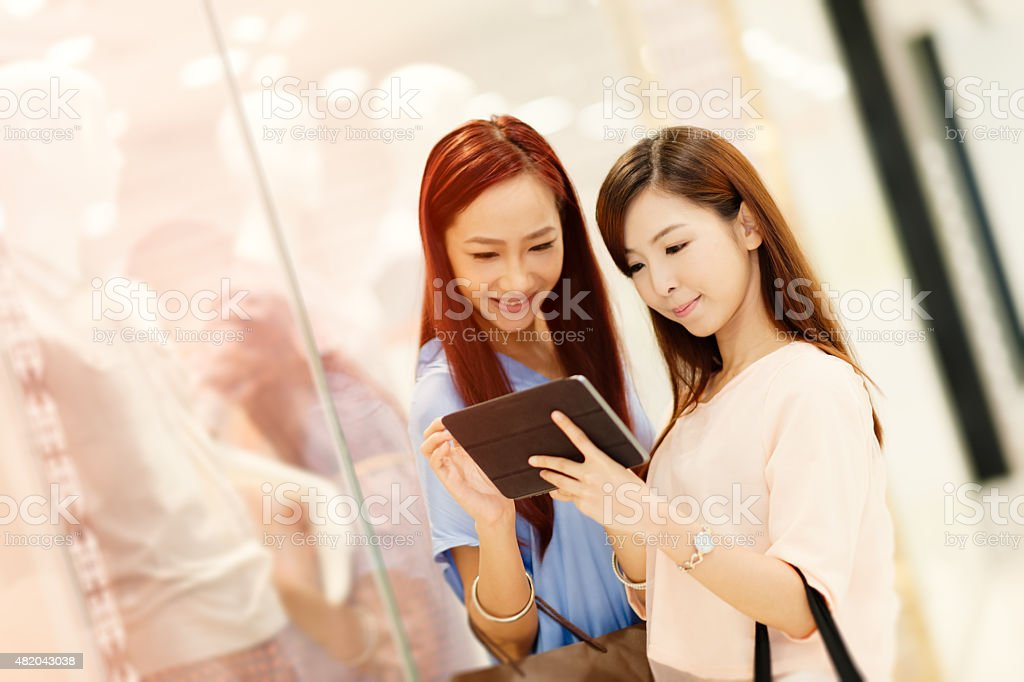 Two Chinese girlfriends in shopping mall stock photo