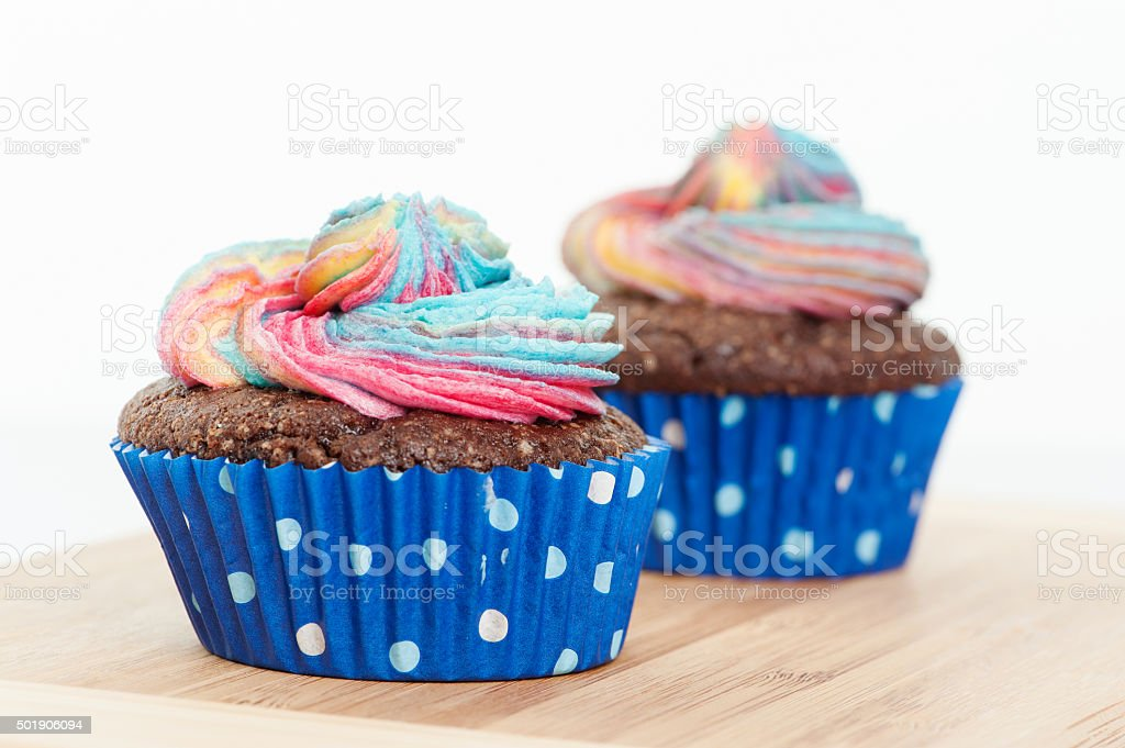 Two Chocolate cupcake with rainbow icing and a yellow candle stock photo