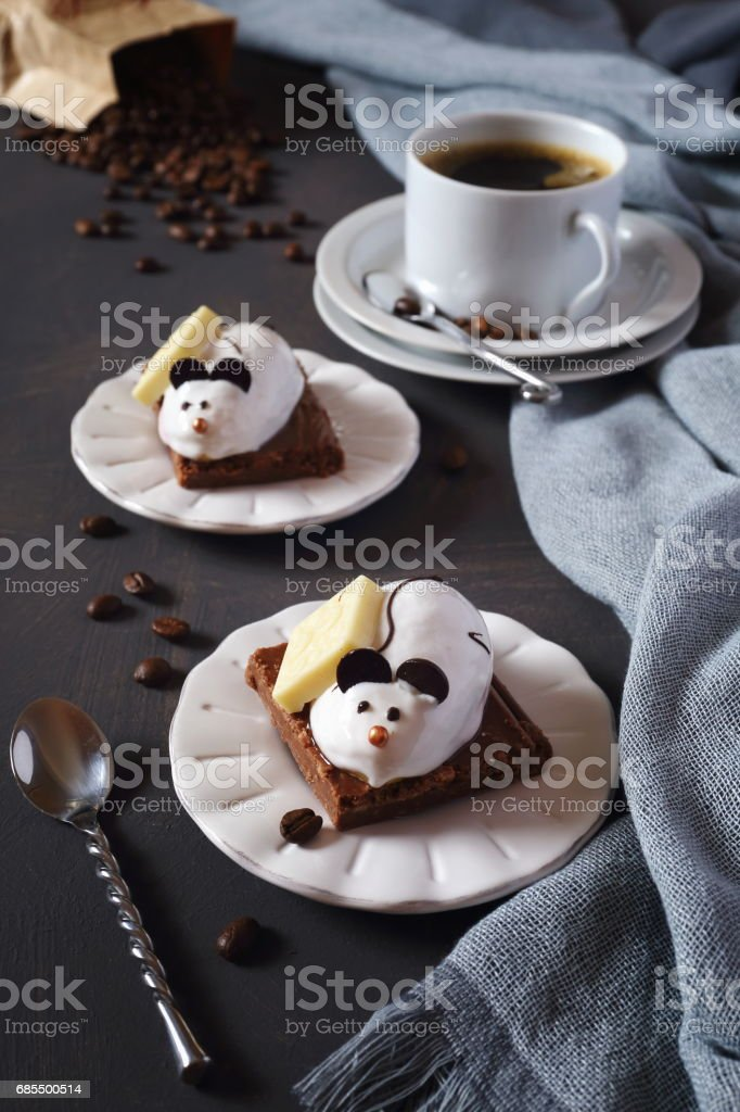 Two chocolate pastry mouse, cup of coffee and coffee beans. Focus...