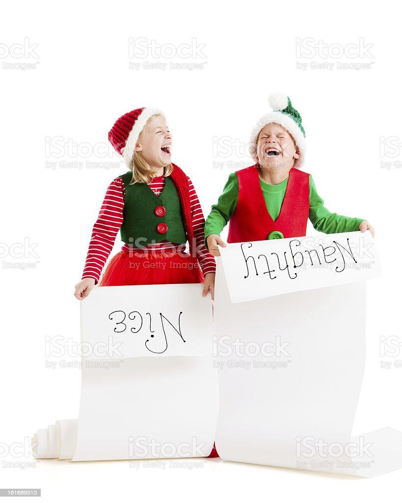 Two Christmas Elves Hold Santas List Naughty and Nice royalty-free stock photo