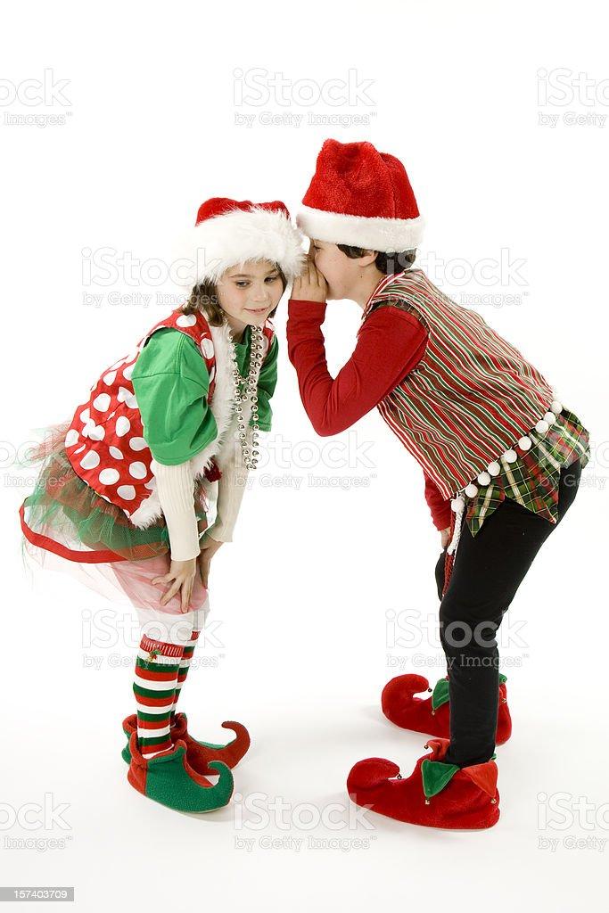 Two Christmas Elves Tell Secrets stock photo