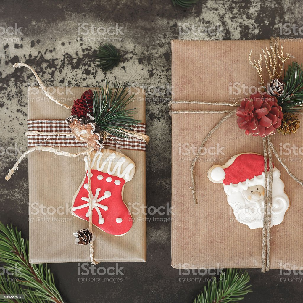 Two Christmas gifts and cookies on rustic board stock photo