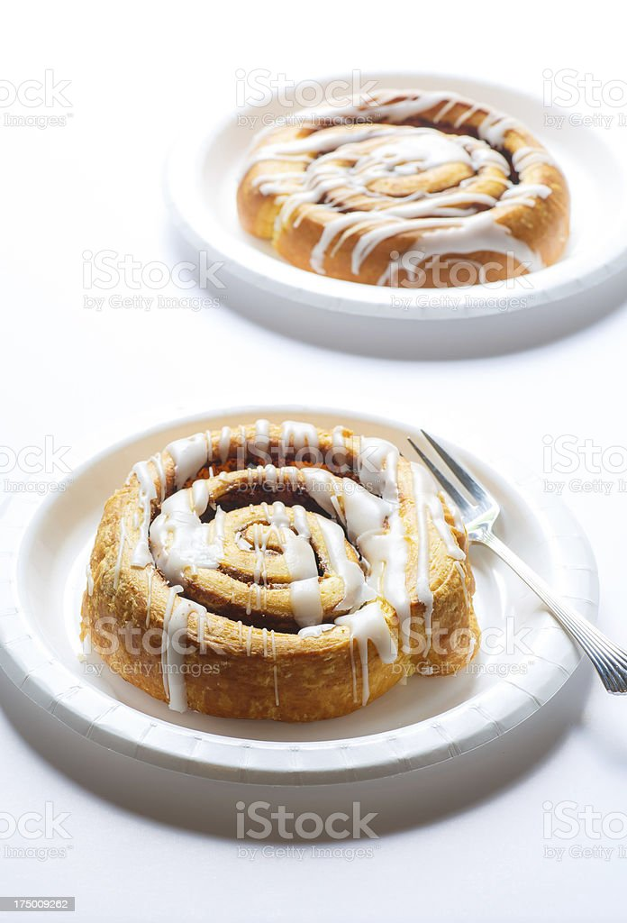 Two Cinnamon Rolls on White Plates royalty-free stock photo