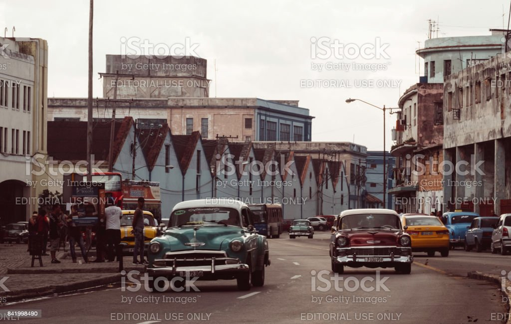 Two classic cars driving on busy street in Cuba with warehouses in background stock photo