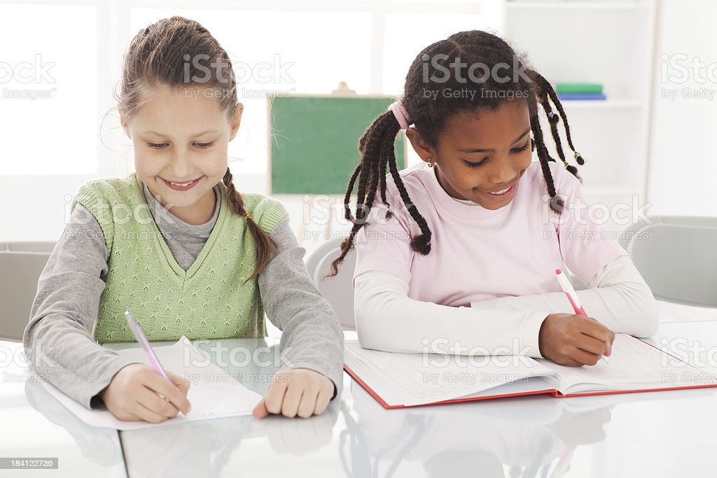 Two classmates writing in their notebooks royalty-free stock photo